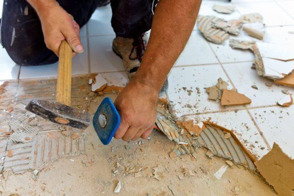 Hand schlägt mit Hammer auf Handmeisel, der alte Fliesen abschlägt